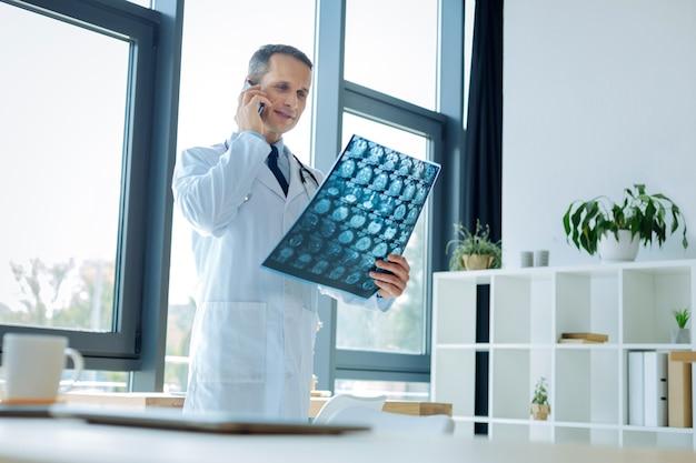 Ciekawy przypadek. poważny, bystry, przystojny lekarz oglądający zdjęcie rentgenowskie i rozmawiający przez telefon, omawiając ciekawy przypadek medyczny