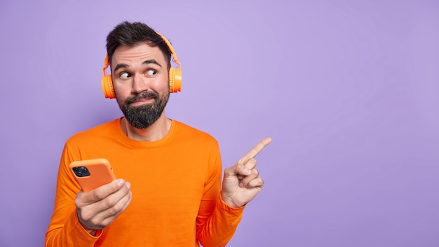 Ciekawy przystojny mężczyzna z brodą demonstruje coś ciekawego w pustej przestrzeni na fioletowej ścianie używa telefonu komórkowego do rozmów online i słuchania muzyki nosi słuchawki ubrane niedbale