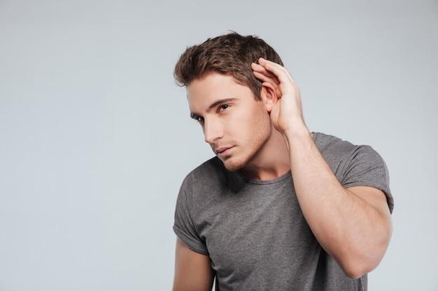 Ciekawy, przystojny młody mężczyzna w koszuli w kratę, podsłuchujący plotki na białym tle