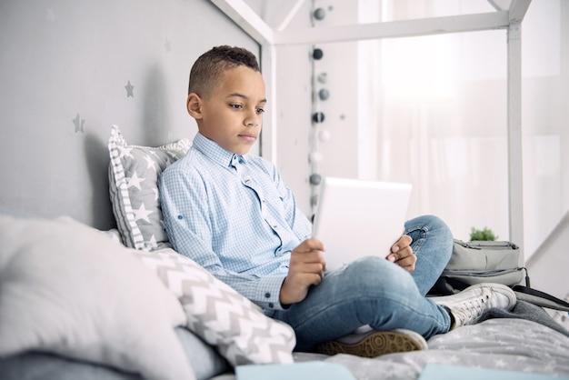 Ciekawy punkt. koncentruje się afro american boy za pomocą tabletu, siedząc na łóżku