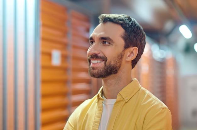 Ciekawy. radosny, atrakcyjny młody brodaty mężczyzna patrzący w górę i uśmiechnięty na bok, kontemplujący z aprobatą stojący w pomieszczeniu
