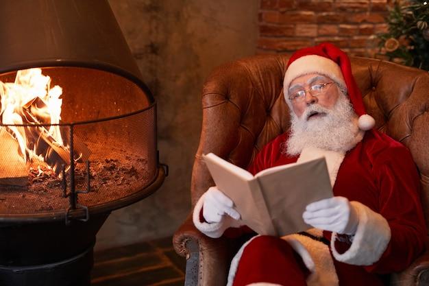 Ciekawy starszy mikołaj w okularach siedzący w wygodnym fotelu przy kominku i odpoczywający z...
