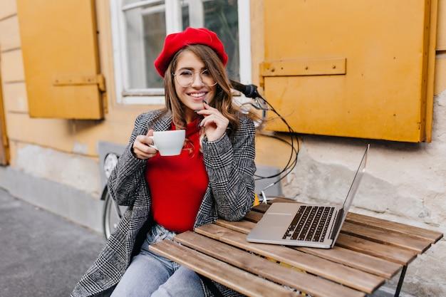 Ciekawy studentka siedzi z laptopem w kawiarni na świeżym powietrzu