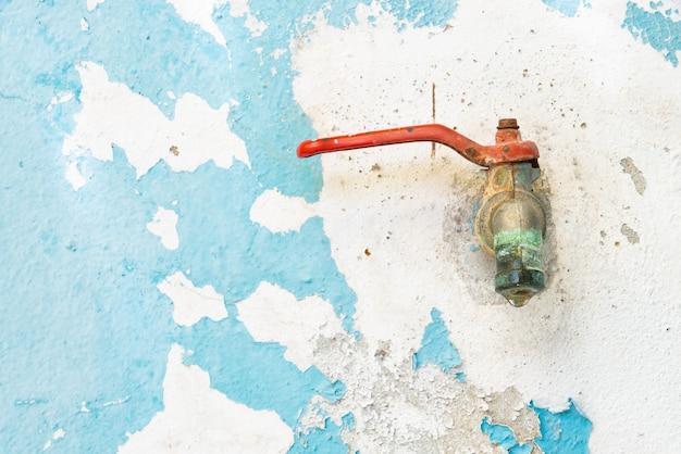 Cieknący kran lub kapiąca woda z kranu na starej ścianie.
