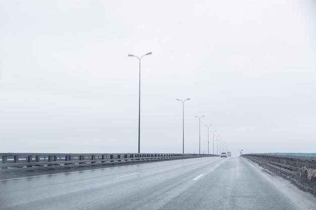 Ciemna autostrada w pochmurną pogodę po deszczu. prosty sposób z dramatycznymi chmurami. pusta autostrada, pochmurne niebo, oświetlenie drogi. podróżuj przy każdej pogodzie.