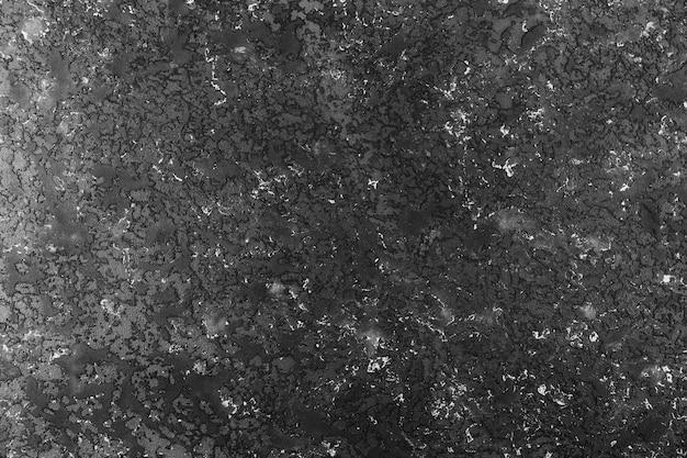 Ciemna betonowa ściana o chropowatej powierzchni