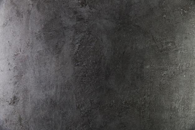Ciemna betonowa ściana o szorstkiej powierzchni