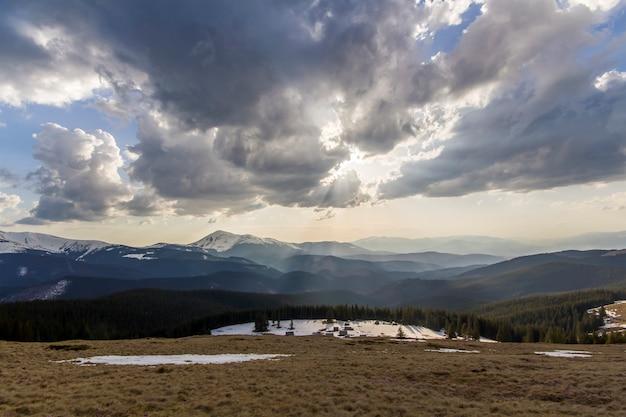 Ciemna burzowa chmura zakrywa niebieskie niebo niskie nad górami