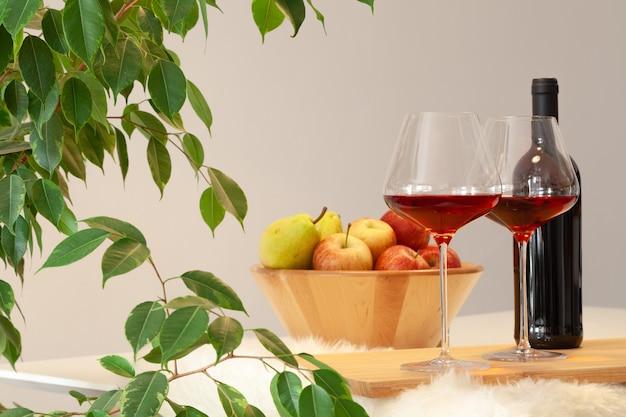 Ciemna butelka i dwie szklanki czerwonego wina, drewniana miska z jabłkami, wazon dekoracyjny na stole w nowoczesnej kuchni