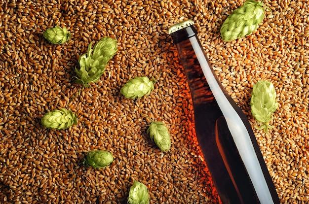 Ciemna butelka piwa na tle na makieta chmielu i pszenicy gotowa do projektu