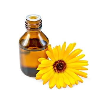 Ciemna butelka z olejkiem aromatycznym, kwiat nagietka z lekkim odcieniem na białym tle