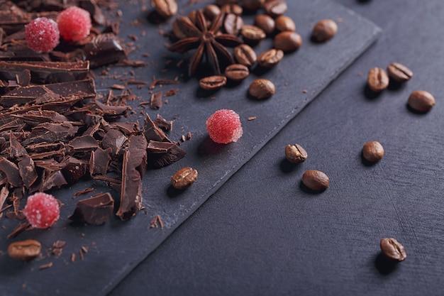 Ciemna czekolada do krojenia, czarne palone ziarna kawy, czerwone jagody z przyprawami na desce łupkowej na czarnym tle tekstury. koncepcja deserów czekoladowych, słodyczy i słodyczy