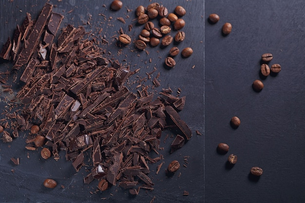 Ciemna czekolada do krojenia, czarne palone ziarna kawy na pokładzie łupków na czarnym tle tekstury. koncepcja deserów czekoladowych, słodyczy i słodyczy
