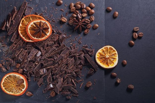 Ciemna czekolada do krojenia, czarne palone ziarna kawy, suszone plasterki cytryny z anyżem przyprawy na desce łupkowej na czarnym tle. deser czekoladowy, koncepcja wyrobów cukierniczych. widok z góry z miejscem na tekst.