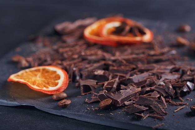 Ciemna czekolada do krojenia, czarne palone ziarna kawy, suszone plasterki cytryny z anyżem przyprawy na desce łupkowej na czarnym tle tekstury. koncepcja deserów czekoladowych, słodyczy i słodyczy