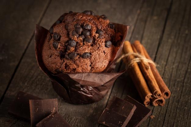 Ciemna czekolada gotowana muffinka z miętą na drewnianym stole z cynamonem, anyżem, czekoladą.