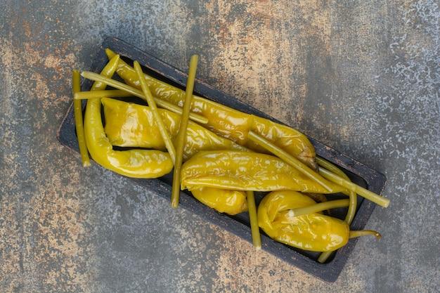Ciemna deska pełna słonych smacznych papryk na marmurowym tle. zdjęcie wysokiej jakości