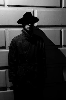 Ciemna dramatyczna sylwetka mężczyzny w kapeluszu i płaszczu przeciwdeszczowym w nocy na ulicy w stylu noir