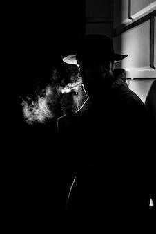Ciemna dramatyczna sylwetka mężczyzny w kapeluszu palenie papierosa nocą na ulicy w stylu noir