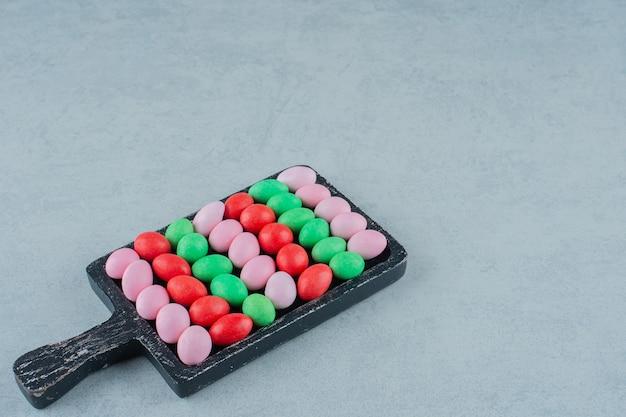 Ciemna drewniana deska pełna okrągłych słodkich kolorowych cukierków na białej powierzchni