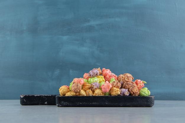Ciemna drewniana deska pełna słodkiego, różnokolorowego popcornu.