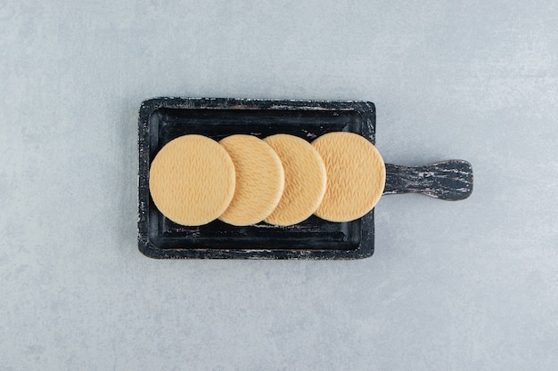 Ciemna drewniana deska ze słodkimi okrągłymi ciasteczkami.