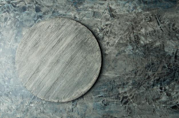 Ciemna drewniana taca na porysowanej czarnej powierzchni