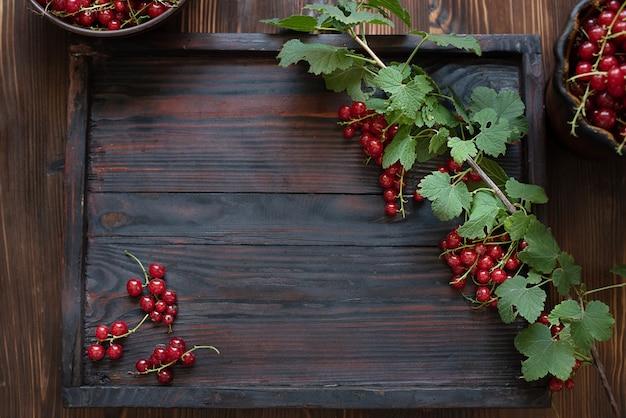 Ciemna drewniana taca z gałęzią dojrzałej czerwonej porzeczki, świeże jagody, koncepcja lato, styl rustykalny, zbliżenie