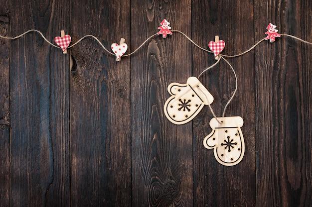 Ciemna drewniana tekstura i świąteczne zabawki w postaci rękawiczek i miejsca na tekst.