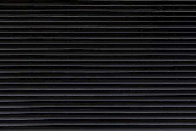 Ciemna falista metalowa powierzchnia dla ściennego tła.