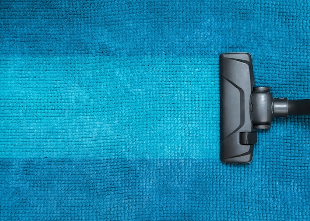 Ciemna główka nowoczesnego odkurzacza używanego podczas odkurzania dywanu.