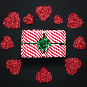 Ciemna kartka walentynkowa z czerwonymi sercami i prezentem świątecznym z zieloną wstążką. walentynki lub święto walentego.