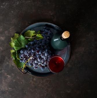 Ciemna kiść winogron z kroplami wody w słabym świetle