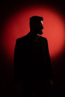 Ciemna męska sylwetka. sylwetka mężczyzna z brodą nad czerwonym tłem z kopii przestrzenią