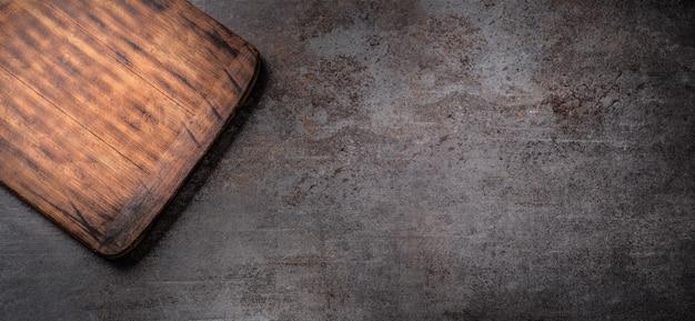 Ciemna metaliczna powierzchnia z prostokątną pustą drewnianą deską do krojenia w lewym górnym rogu