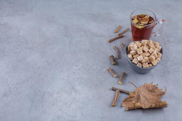 Ciemna miska kostek cukru brązowego i filiżanka herbaty na kamiennej powierzchni.
