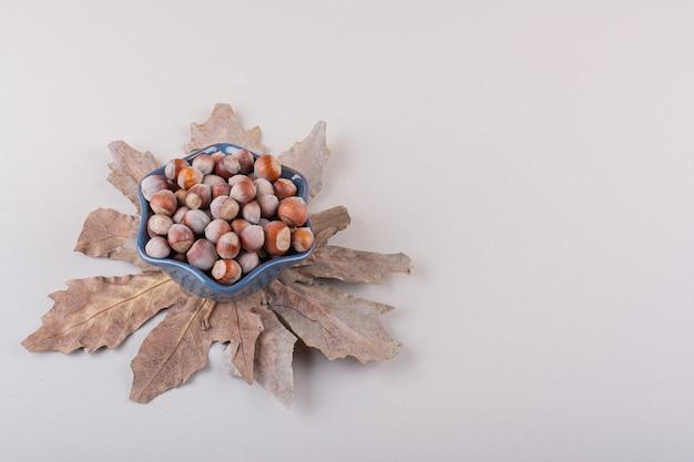 Ciemna miska łuskanych naturalnych orzechów laskowych i suchych liści na białym tle. zdjęcie wysokiej jakości