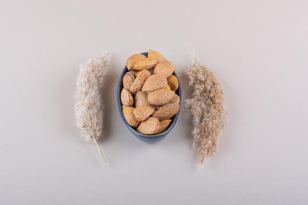Ciemna miska łuskanych organicznych migdałów na białym tle. zdjęcie wysokiej jakości