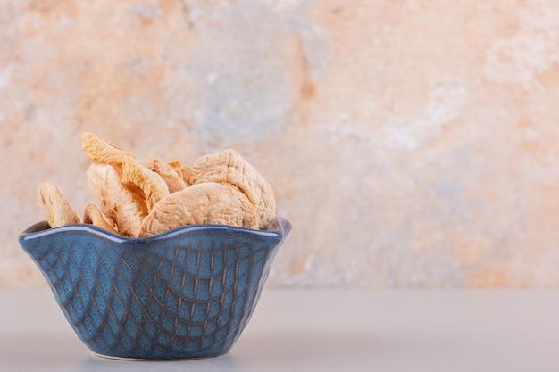 Ciemna miska z suchymi krążkami jabłek umieszczona na białym stole. wysokiej jakości zdjęcie