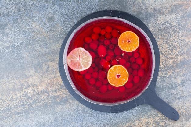 Ciemna patelnia czerwonego soku na marmurowym tle. zdjęcie wysokiej jakości