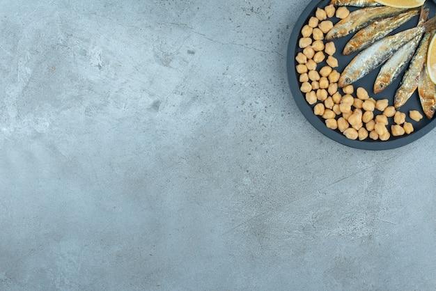 Ciemna patelnia z rybą i groszkiem na szarym tle. zdjęcie wysokiej jakości