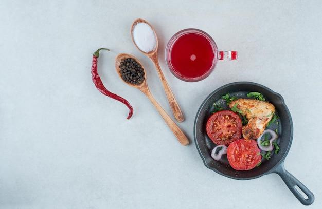 Ciemna patelnia ze smażonymi plastrami pomidora i kurczaka na białym stole.