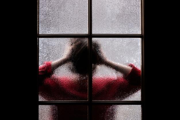 Ciemna sylwetka dziewczyny w czerwieni za szkłem.