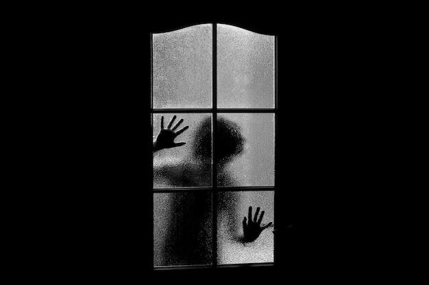 Ciemna sylwetka dziewczyny za szkłem. zamknięty samotnie w pokoju za drzwiami na halloween w skali szarości. koszmar dziecka z kosmitami, potworami i duchami. zło w domu w trybie monochromatycznym. w nawiedzonym domu.