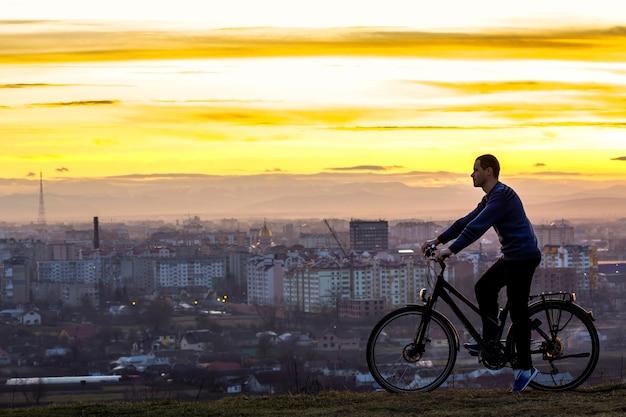 Ciemna sylwetka mężczyzny stojącego w pobliżu roweru z nocą