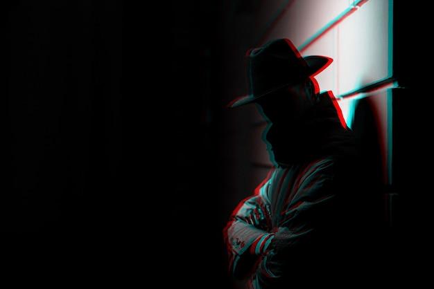 Ciemna sylwetka mężczyzny w płaszczu przeciwdeszczowym z kapeluszem w nocy