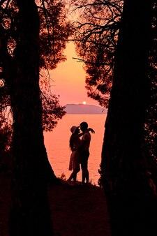 Ciemna sylwetka przytulającej się para zakochanych w pobliżu morza