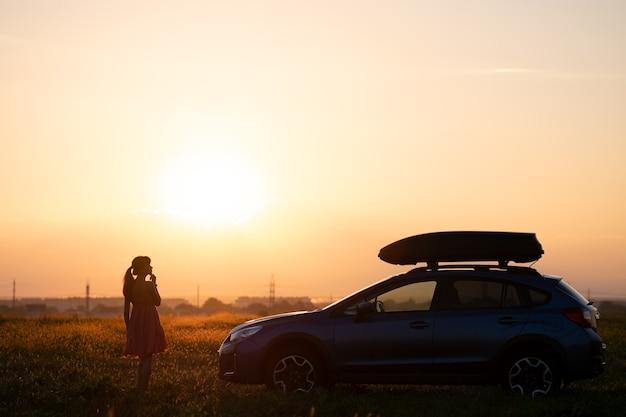 Ciemna sylwetka samotnej kobiety relaks w pobliżu jej samochodu na trawiastej łące, ciesząc się widokiem kolorowy wschód słońca. młoda kobieta kierowca odpoczywa podczas podróży obok pojazdu suv.