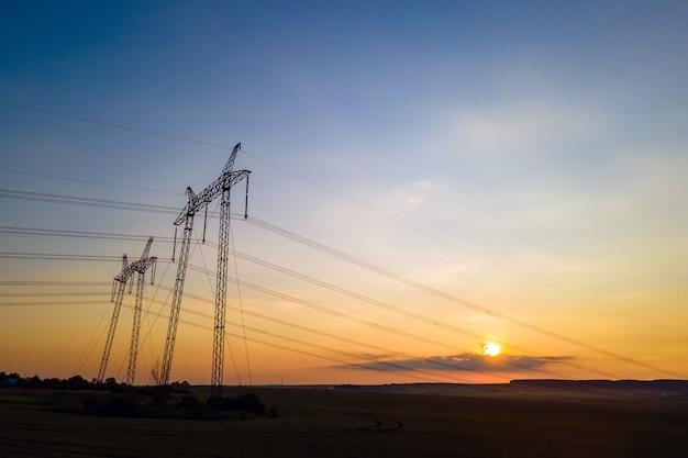 Ciemna sylwetka wież wysokiego napięcia z liniami energetycznymi o wschodzie słońca.