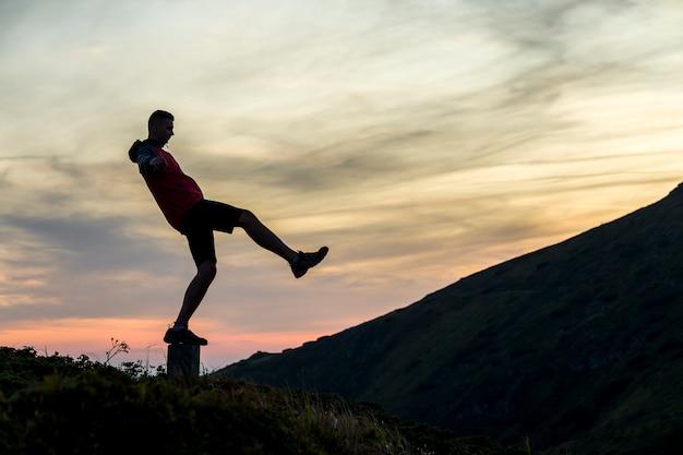 Ciemna sylwetka wycieczkowicz balansujący na kamieniu szczytu w wieczornych górach.